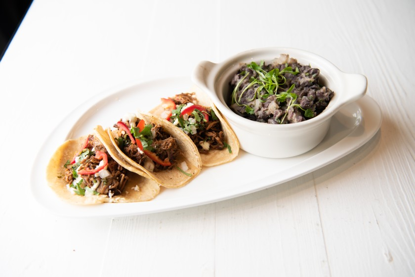 Lamb tacos, served with a side of black beans, can be paired with a pint for $10 at Kairoa Brewing Co. in University Heights.(Elizabeth Zaranka)